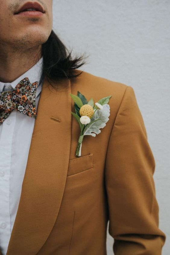a cool boho fall groom's look with a yellow tux, a white shirt, a floral bow tie and a floral boutonniere