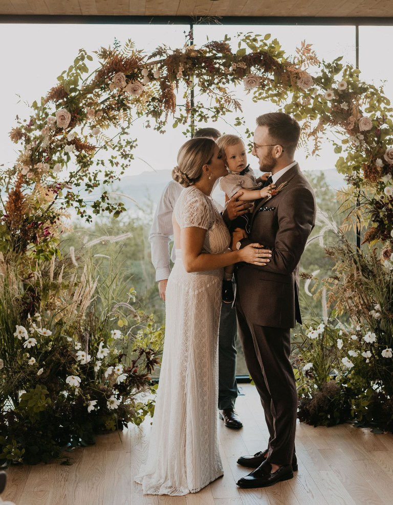 The bride was wearing a boho lace sheath wedding dress with a cutout back, the groom was wearing a brown suit