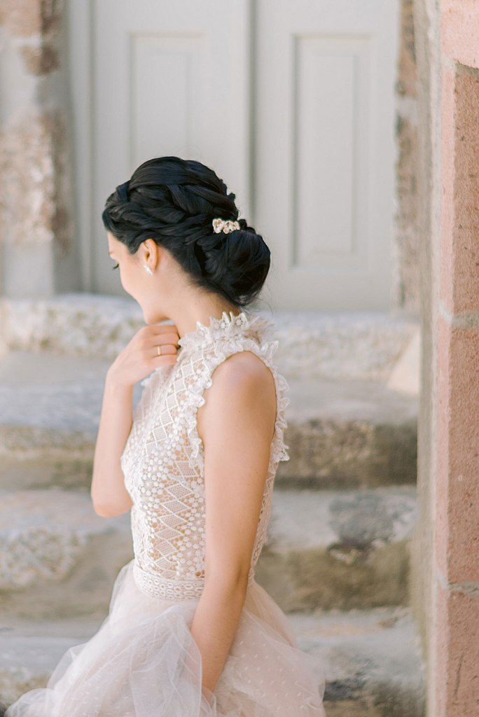 The bride was wearing a gorgeous sleeveless wedding dress with a lace bodice, a high neckline and a blush lace skirt
