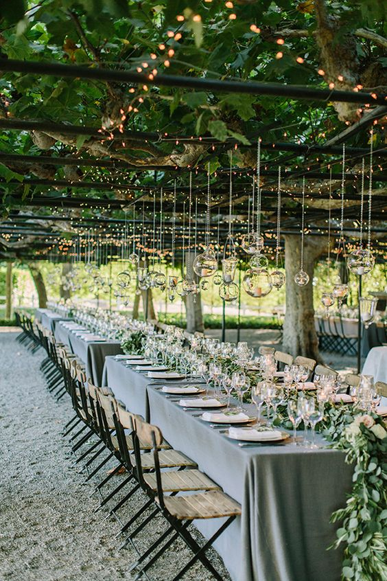 a beautiful outdoor wedding reception space with a grid, greenery, lights and hanging candle holders is amazing