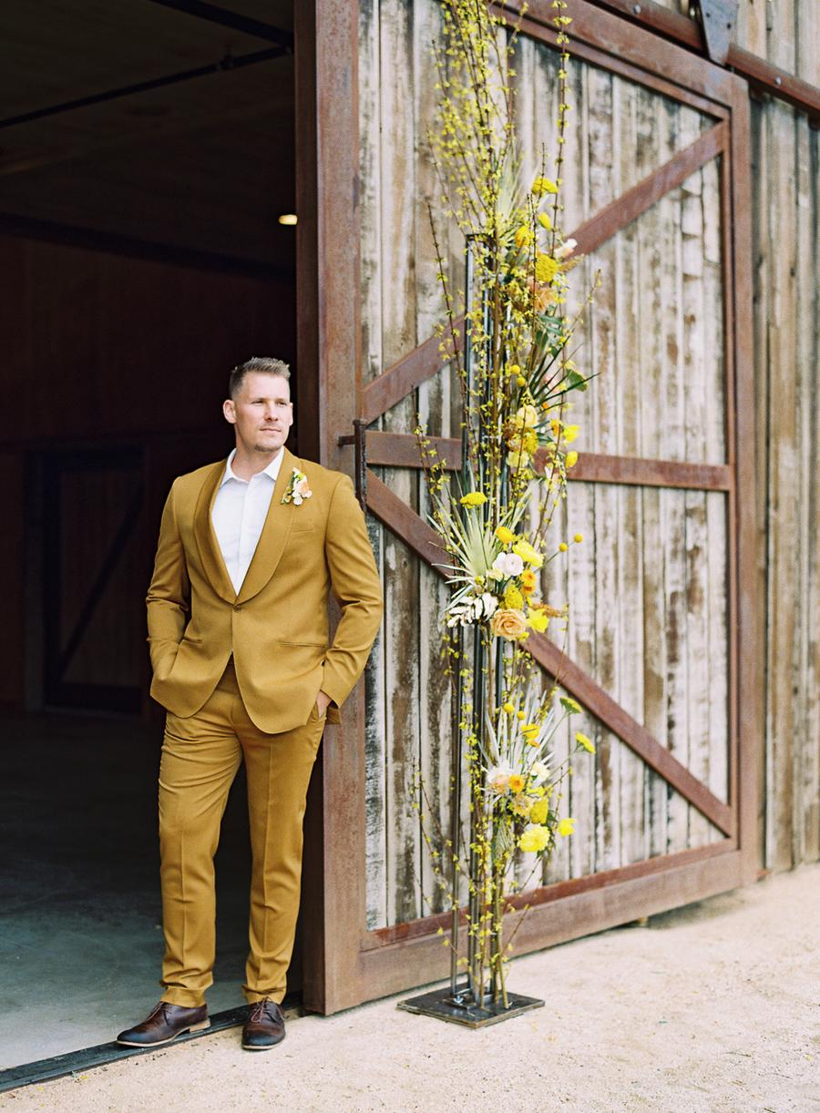 a stylish groom's look with a mustard tux, brown shoes, a white shirt and a floral boutonniere for a spring wedding