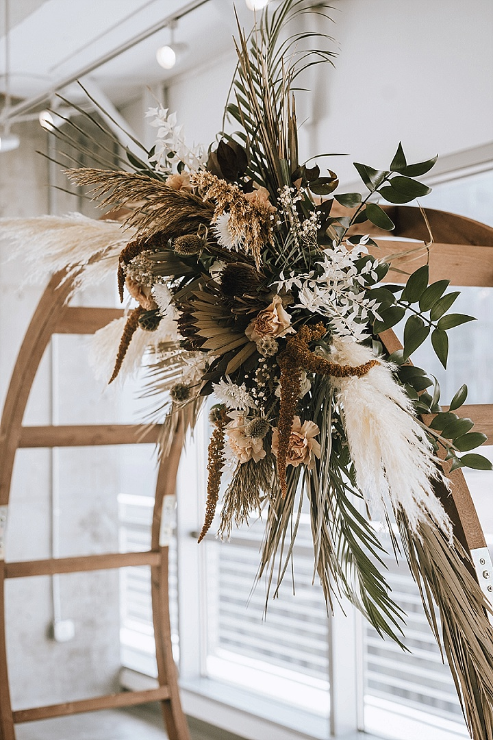 The wedding arch was a round wooden one, with greenery, dried blooms and grasses