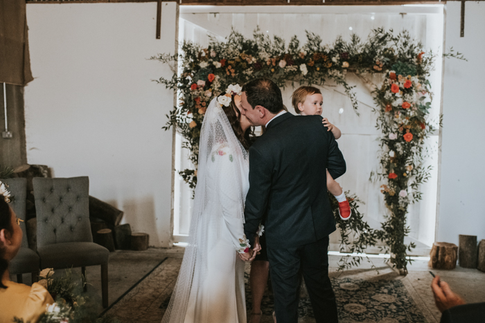 The wedding arch was done with greenery and bright blooms