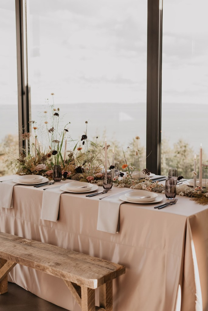 The wedding tablescape was done with blush and white linens, white candles, orange and dark blooms and greenery