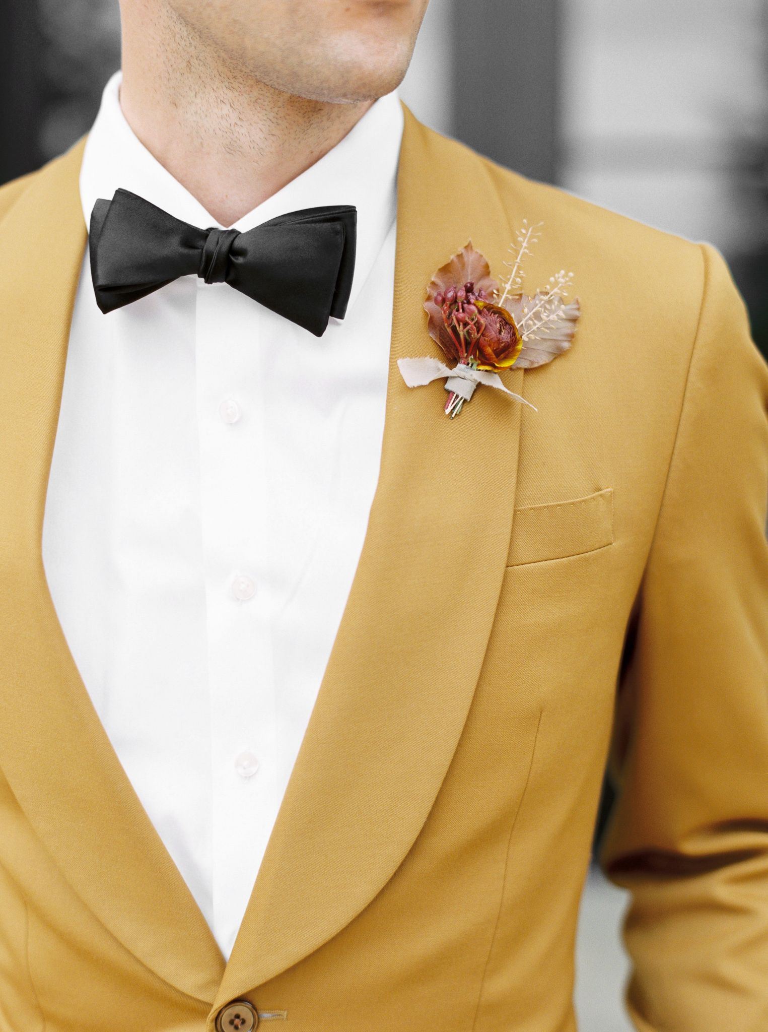 a yellow tux, a white shirt and a black bow tie for a chic fall wedding