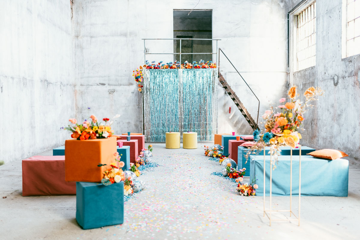 The wedding ceremony space was made very colorful, with bright cubes and blooms and a shiny backdrop