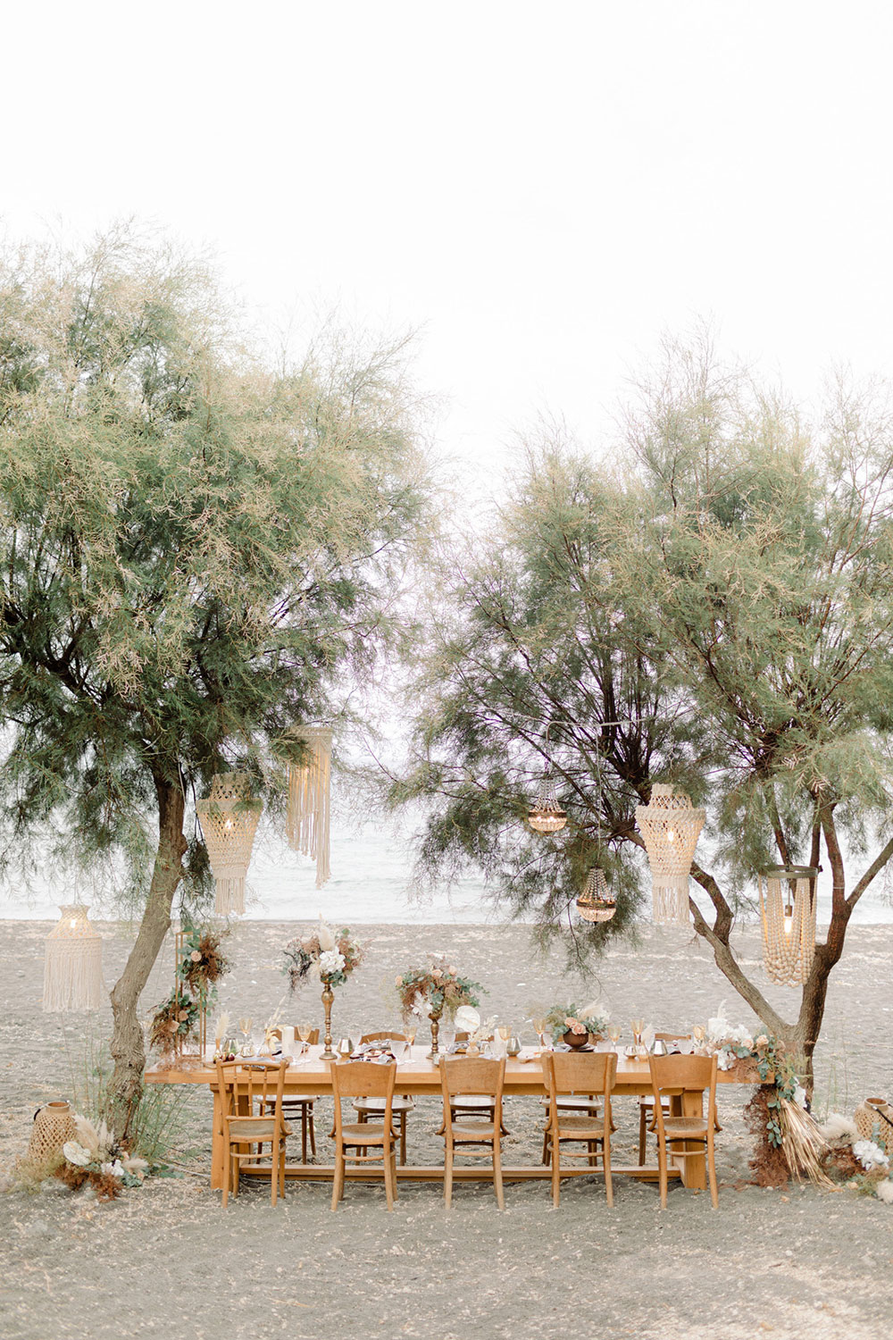 The wedding reception space was organized right on the beach, with trees, blooms and greenery
