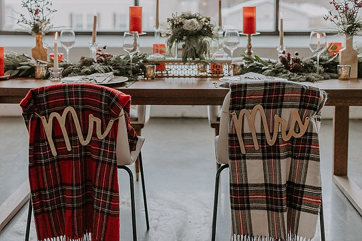 The wedding tablescape was done with greenery, berries, red and white candles, branches and there were plaid blankets