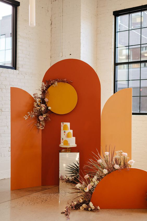 a bold 70s inspired wedding backdrop in orange, red and buttermilk, neutral blooms and a bold wedding cake