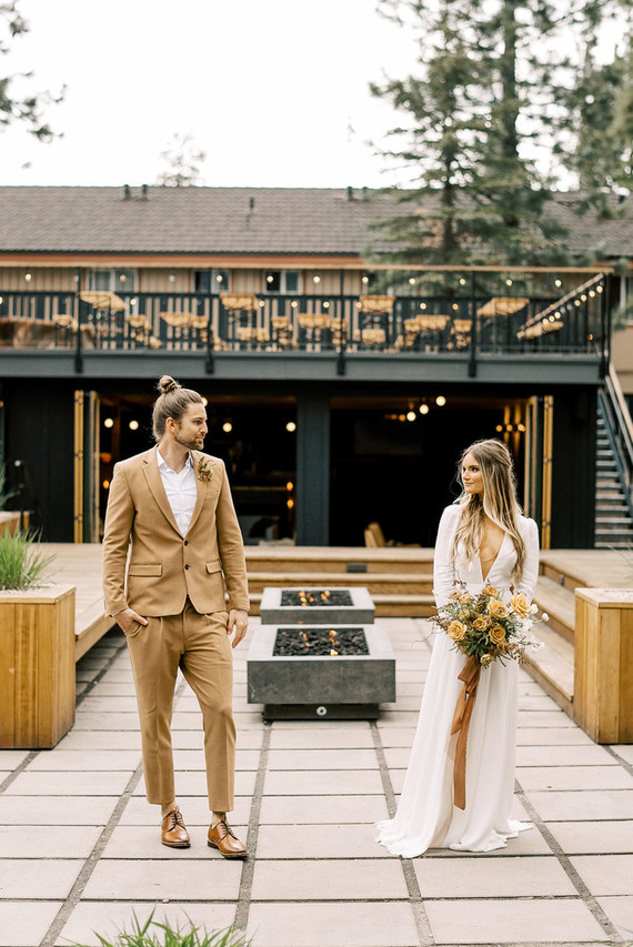 an ocher groom's suit, a white shirt, brown shoes, a dried flower boutonniere and a top knot for a boho fal wedding