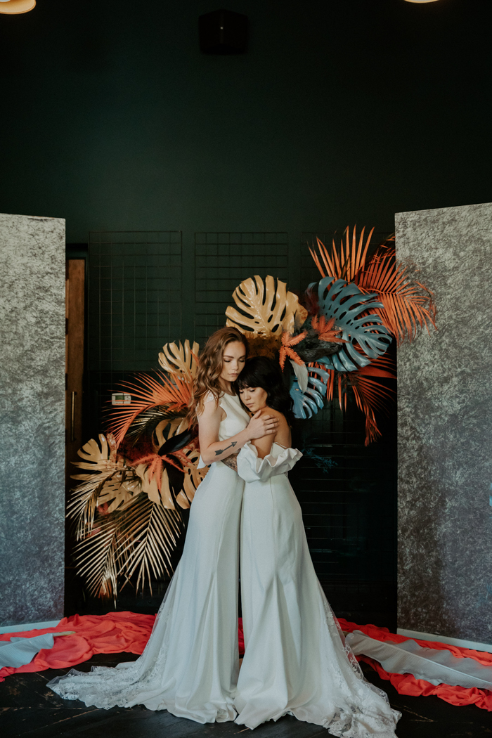 The wedding backdrop showed off an installation of gold, orange and blue leaves and fronds and marble backdrops