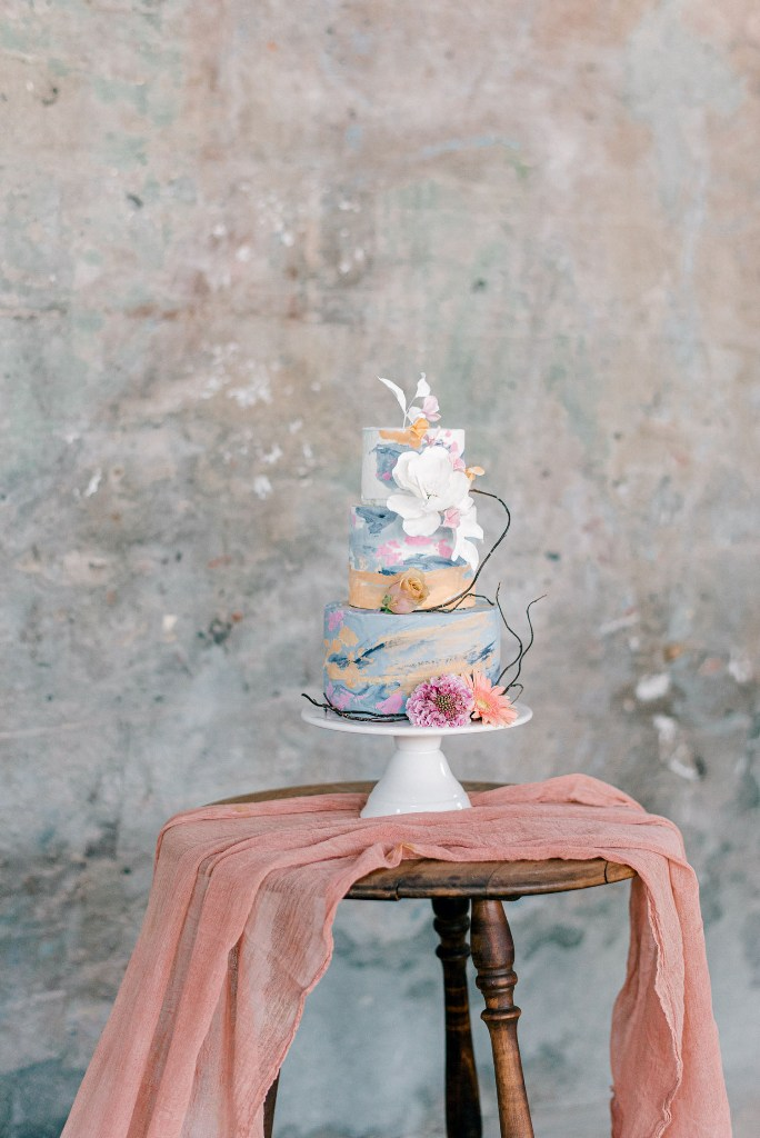 The wedding cake was decorated with bold watercolors and twigs and blooms