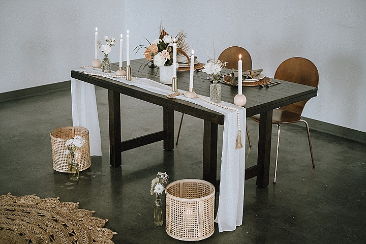 The wedding table was uncovered with a table runner, wicker placemats, candles, fresh and dried blooms and wooden beads