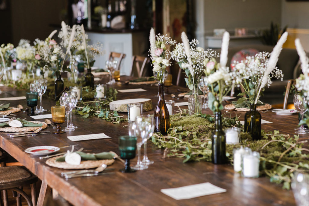 The wedding tablescape was done with greenery, moss and white blooms and feathers, green and amber glasses