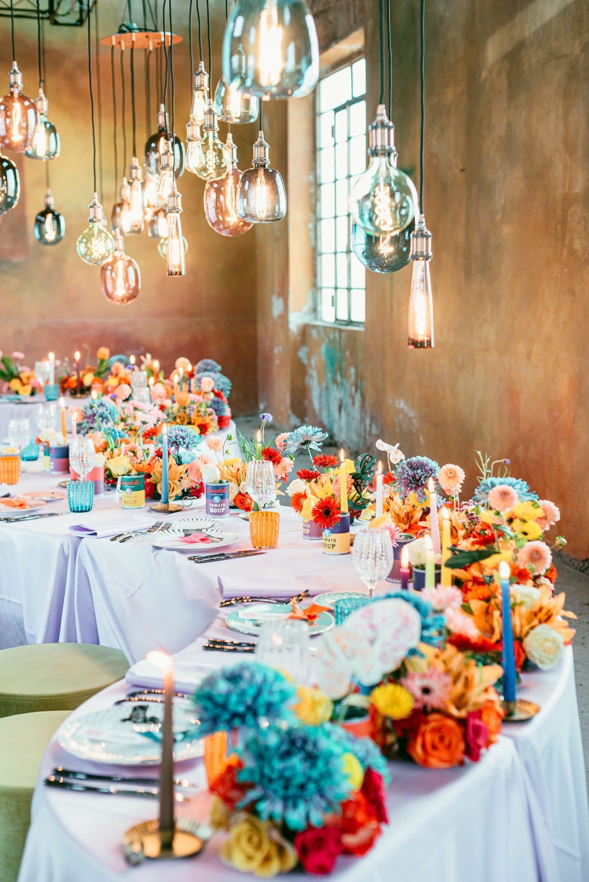 This wedding reception space is so cool, with a colorful long table, bold candles and blooms and hanging bulbs