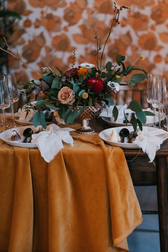 a refined wedding reception table with a rust velvet tablecloth, bold blooms and greenery and refined porcelain and cutlery