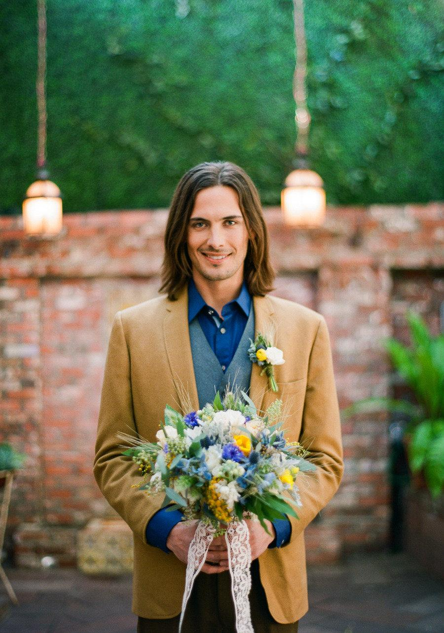 a whimsy groom's look with a navy shirt, a grey waistcoat, a mustard blazer and brown pants for a bold and chic look