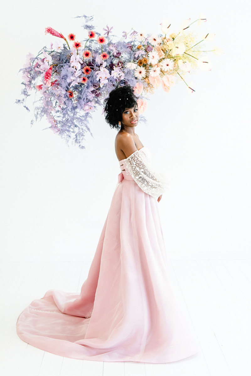 The bride was wearing a gorgeous off the shoulder wedding dress with a lace bodice and sleeves and a pink layered skirt with a train