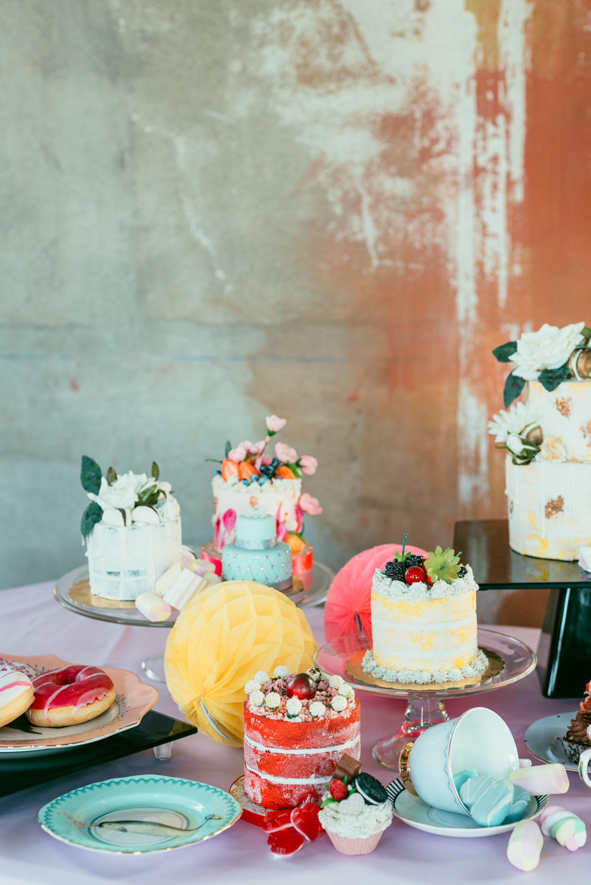 The wedding dessert table showed off adorable colorful cakes, donuts and other desserts