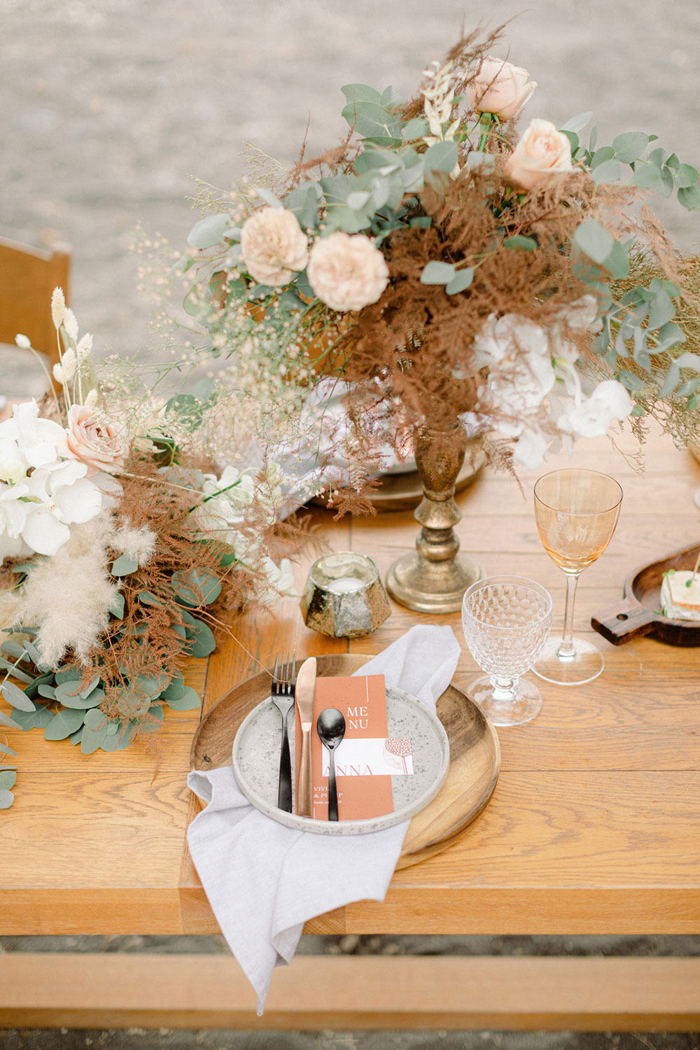 The wedding reception space was done with wooden chargers, rust menus and amber glasses, chic centerpieces with blush blooms and rust leaves and greenery