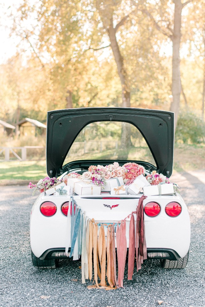 What lovely wedding car decor with a rainbow fabric banner and bold blooms