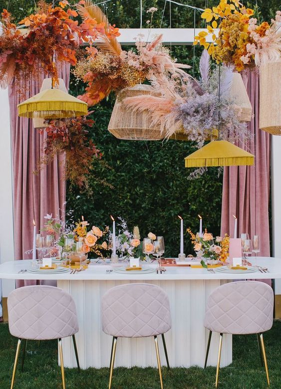 a bold wedding reception space with lavender chairs, bold yellow fringe lamps and bold orange and red blooms