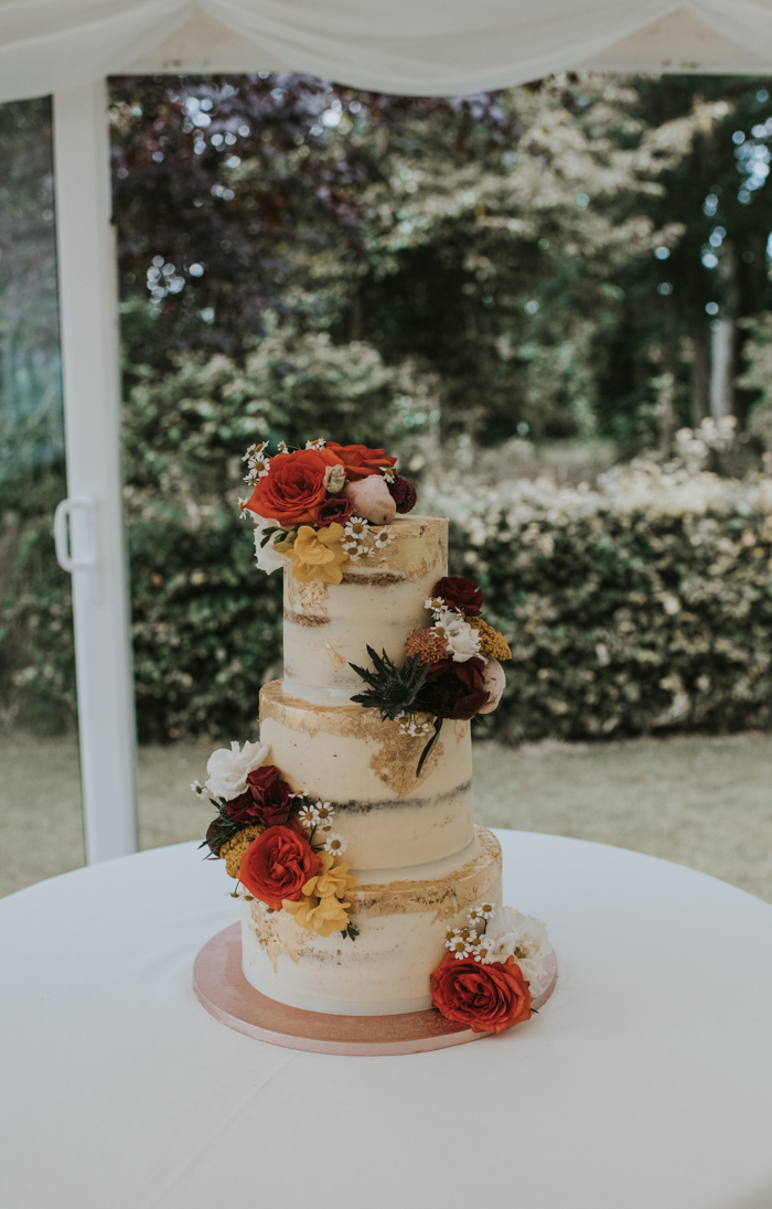 The wedding cake was a naked one, with bright blooms and edible gold