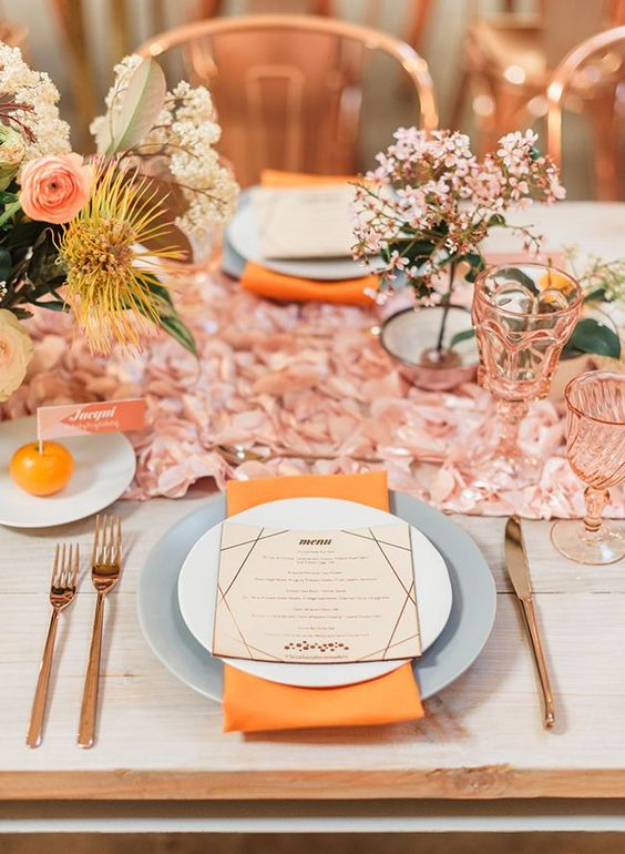 a cheerful wedding tablescape with a rose table runner, grey plates, orange napkins, pink glasses, bold and pastel blooms