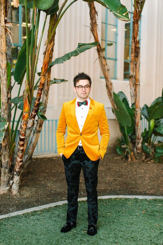 10 a groom wearing a whimsical outfit with a white shirt, a colorful bow tie, black flroal print pants and a bright yellow blazer