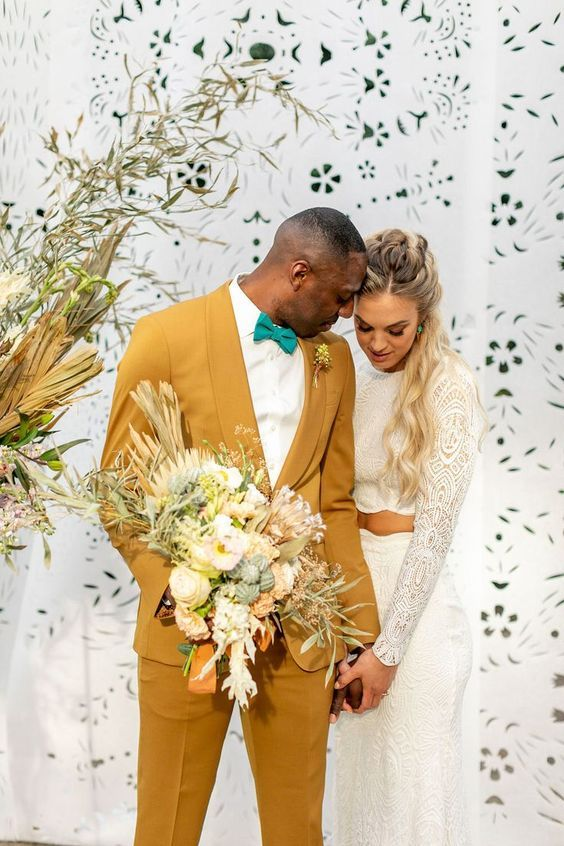 a gorgeous groom's look with a yellow tuxedo, an emerald bow tie and a white shirt for a summer or boho wedding