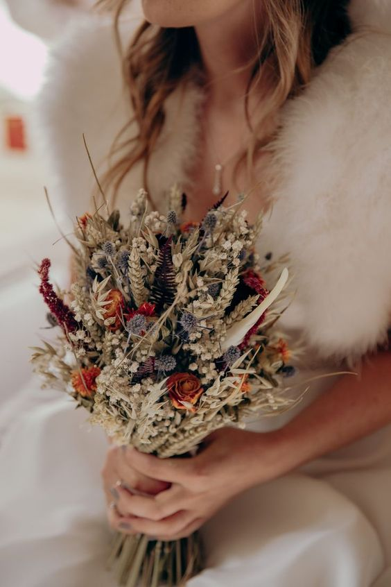 a dreamy dried bloom wedding bouquet with orange, red, lavender and neutral blooms and grasses
