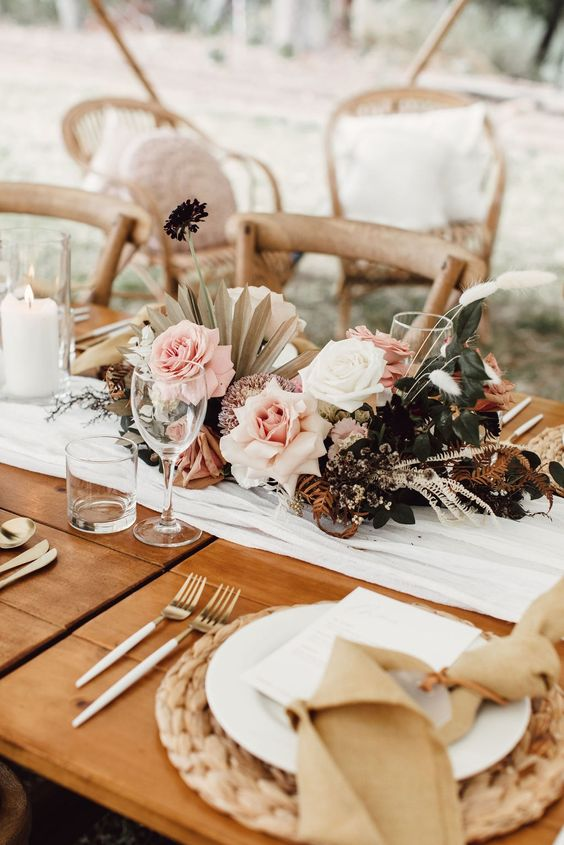 a chic fresh and dried bloom wedding centerpiece with greeneyr, grasses and fronds, with blush roses is elegant