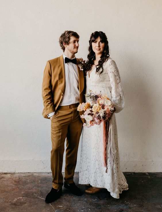 a mustard wedding suit, a white shirt, a black bow tie and black loafers for a refined and very chic look at the wedding