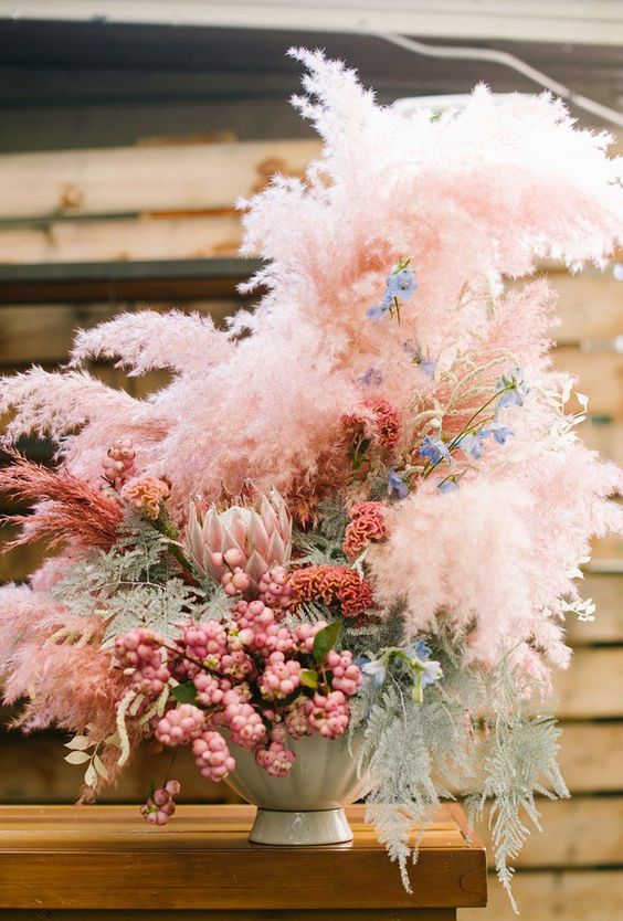 a wedding floral arrange,ent with pink grasses, king proteas, dried and fresh blooms and berries is wow