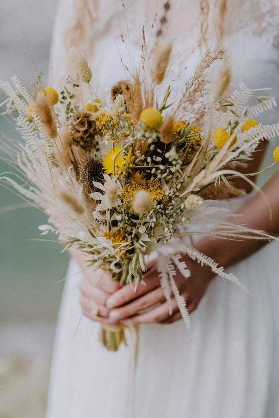 a bright boho wedding bouquet with yellow and neutral blooms and grasses is a very statement idea