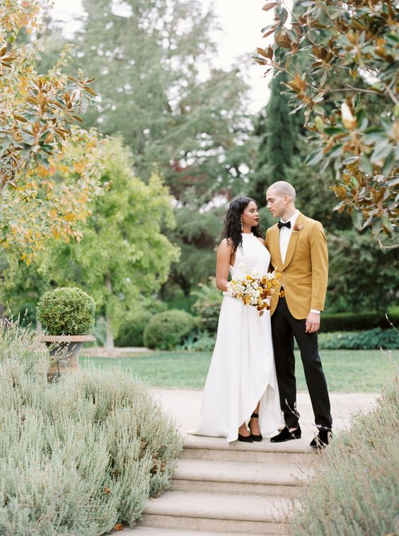 an elegant groom's look with a yellow tux, black pants, a bow tie and loafers is very refined and chic