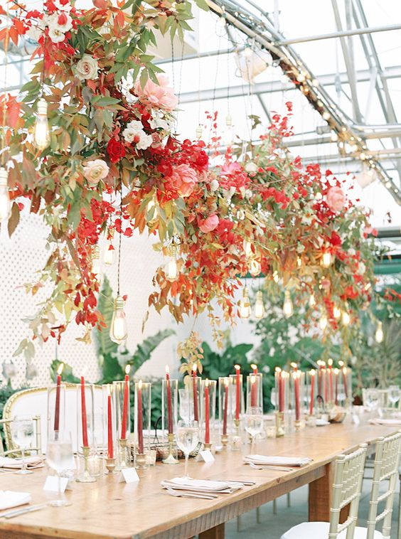 a bold overhead floral installation in deep red, pink, neutrals, berries, blush blooms, greenery and bulbs