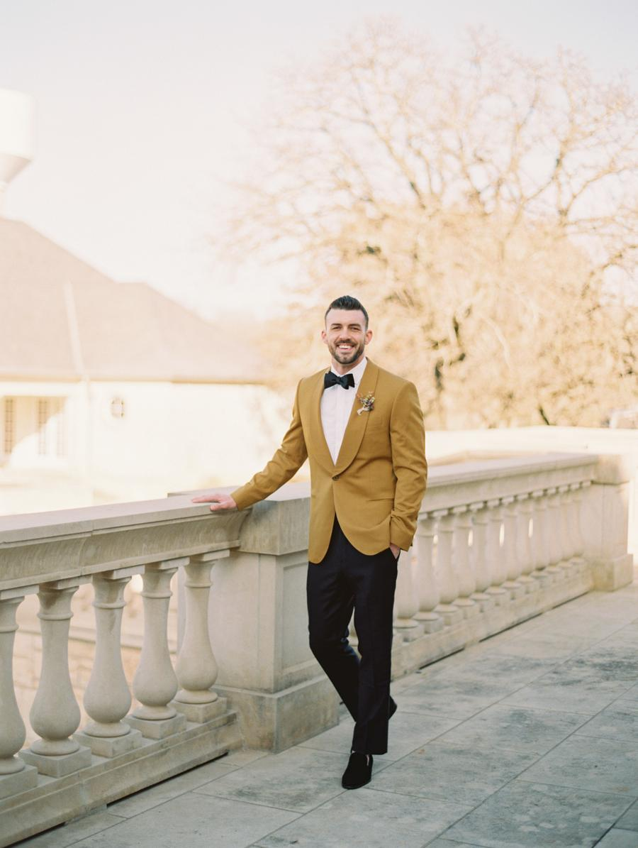 a refined groom's look with an ochre tux, black pants, loafers and a bow tie and a dried flower boutonniere