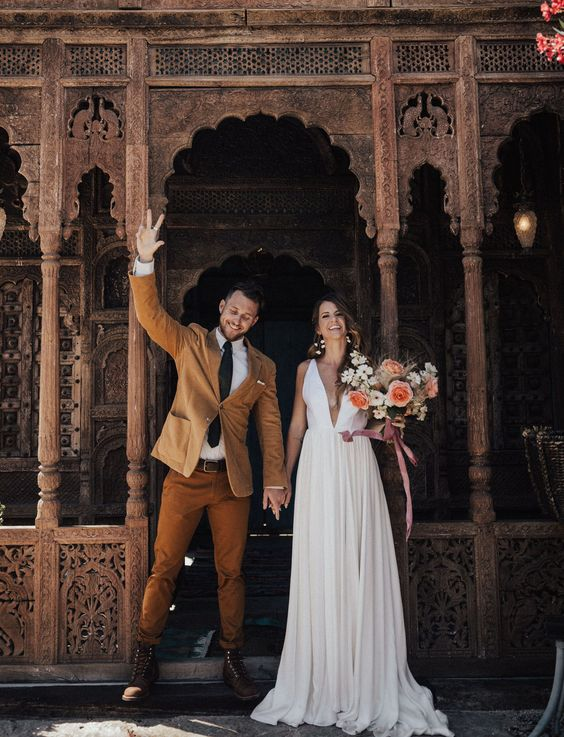 a boho fall groom's look with a yellow blazer, rust colored pants, brown boots, a black tie and a white shirt is cool