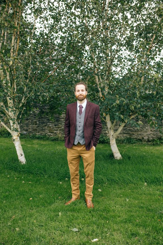 a boho groom's look with a burgundy blazer, a grey vest, a white shirt, a burgundy tie, mustard pants, brown shoes