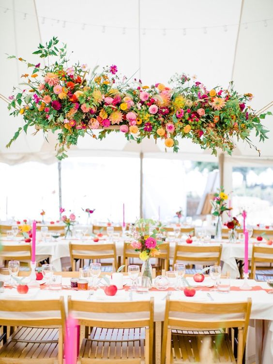 a bright floral wedding installation of yellow, pink, fuchsia blooms and greenery is a very cheerful idea