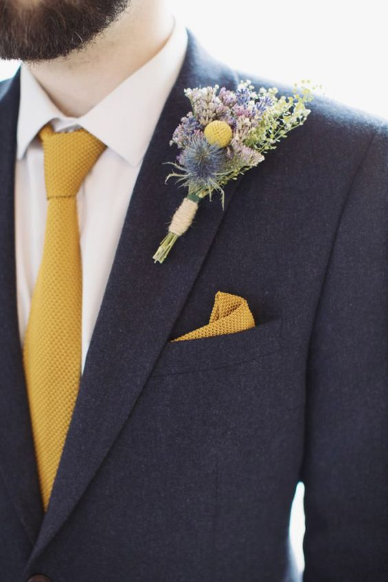 21 an elegant graphite grey suit, a white shirt, a yellow tie and pocket square plus a bold floral boutonniere