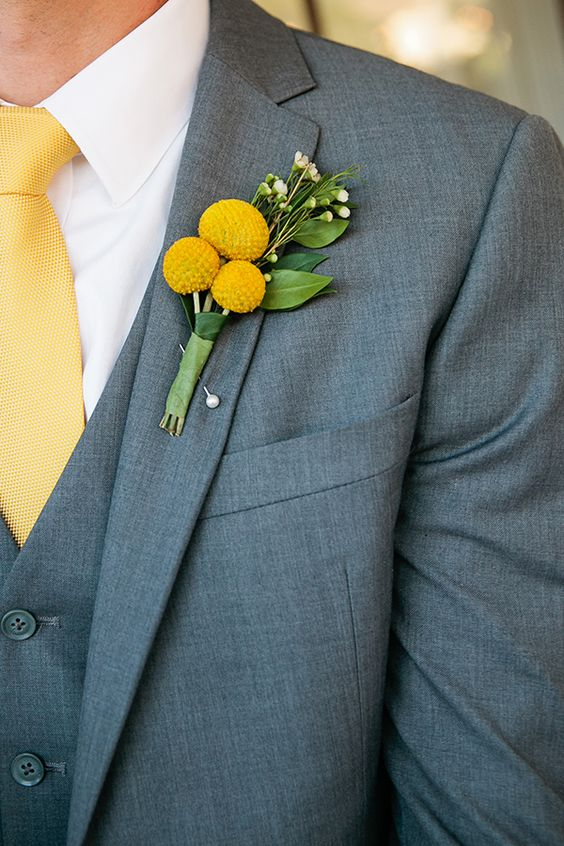 a stylish grey three-piece suit, a yellow tie and a billy ball boutonniere for an elegant and cool look