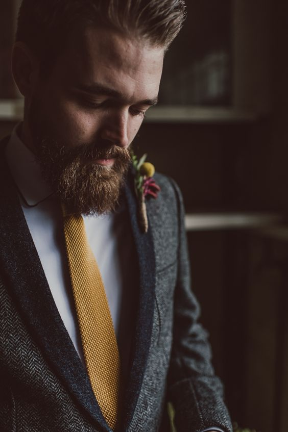 a chic boho groom's look with a grey tux with black lapels, a mustard tie and a white shirt plus a bold boutonniere