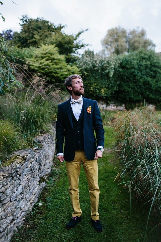 a bright and chic look with a white shirt, a black vest, a navy blazer, mustard pants, a floral bow tie and black shoes