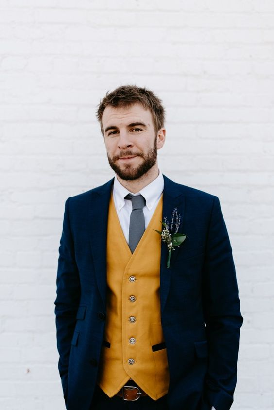 a bold groom's look with a navy suit, a mustard waistcoat, a grey tie, a white shirt is a very bright and chic idea