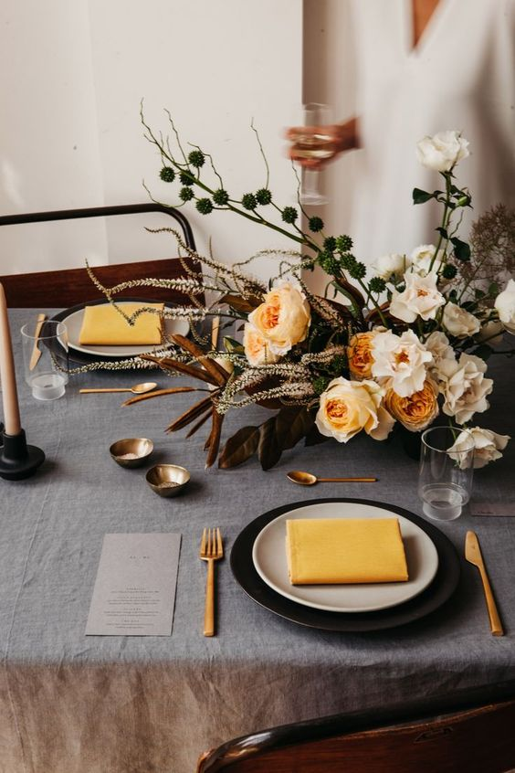 a beautiful wedding tablescape with a grey tablecloth, black and white plates, mustard napkins, chic cutlery and a lovely peachy and white wedding centerpiece