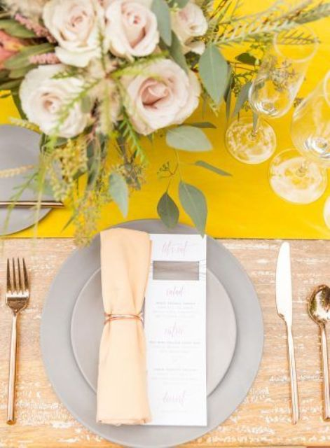 a chic wedding table setting with a yellow table runner, grey plates, peachy napkins, blush blooms and greenery