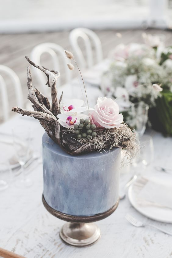 a coastal grey wedding cake with driftwood, hay, bright blooms, graases and berries is a very nonchalant and chic idea