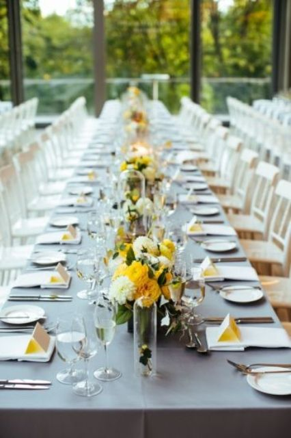 a contemporary wedding tablescape with a grey tablecloth, white napkins, yellow cards and yellow and neutral blooms